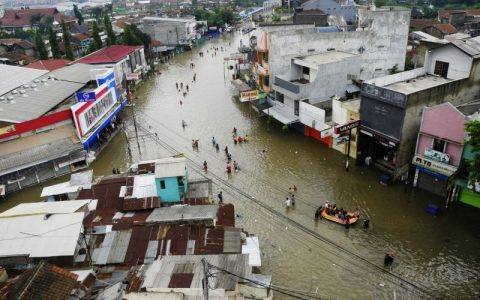 Sejumlah warga dan perahu karet berjalan melewati genangan banjir di Jalan Raya Dayeuhkolot, Kabupaten Bandung, Jawa Barat, Sabtu (20/12).